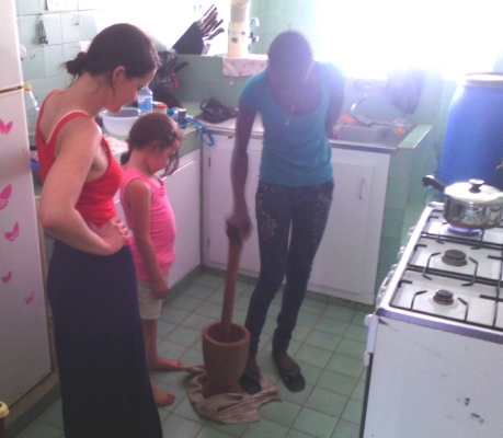 Our house help, Martine, teaching the girls how to use the mortar and pestle.